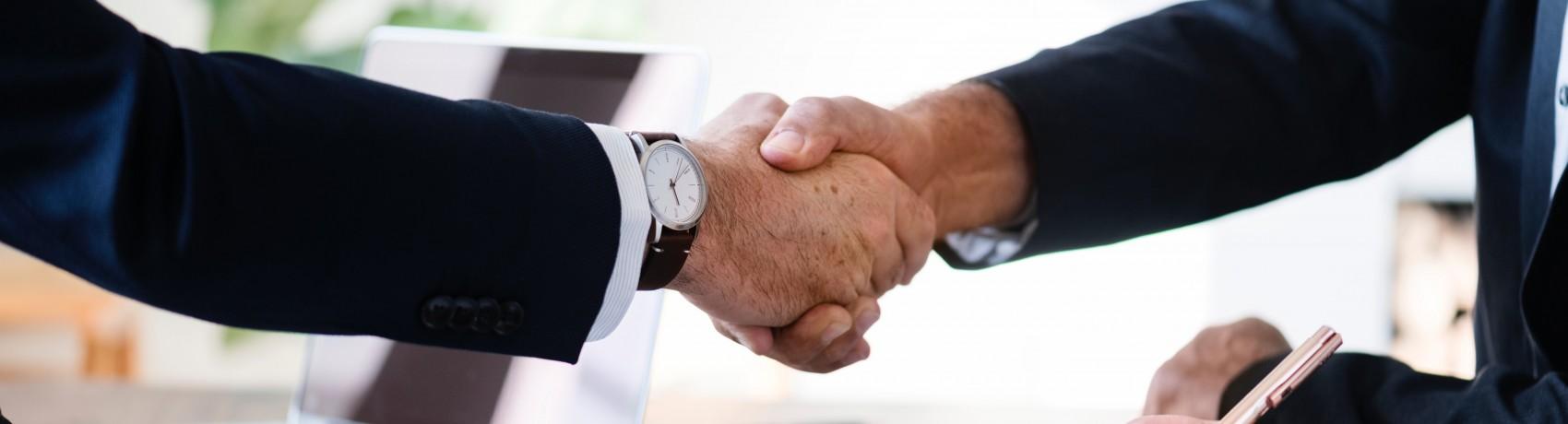 Bild zeigt zwei Sportmanager, die sich die Hand geben und anscheinend eine Kooperation eingegangen sind.